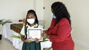 Seriah Laurent of the Ivor Walters Primary School receives Naomi Daniel-Browne Scholarship Award from Mrs. Adina Taylor, sister of the late Naomi Daniel-Browne