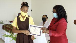 Kailar Isaac of the St. Thomas' Primary School receives Naomi Daniel-Browne scholarship award from Mrs. Adina Taylor, sister of the late Naomi Daniel-Browne