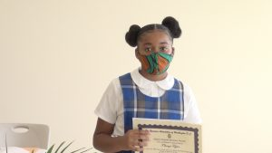 T'shanzi Taylor of the St. James' Primary School after receiving her Naomi Daniel-Browne scholarship award from Mrs. Adina Taylor, sister of the late Naomi Daniel-Browne