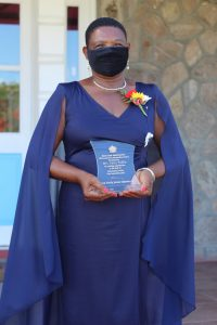 Mrs. Palsy Wilkin showing off her award after receiving the plaque from Her Honour Mrs. Hyleeta Liburd, Deputy Governor General on Nevis after an Awards Ceremony at Government House on September 20, 2021, in honour of her sterling contribution to Education in St. Kitts and Nevis on the occasion of the Federation's 38th Anniversary of Independence