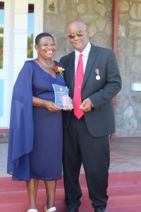 Independence Day Awardee Mrs. Palsy Wilkin with her husband Mr. Pearlievan Wilkin after receiving a plaque from Her Honour Mrs. Hyleeta Liburd, Deputy Governor General on Nevis, at an Awards Ceremony at Government House on September 20, 2021, in honour of her sterling contribution to Education in St. Kitts and Nevis on the occasion of the Federation's 38th Anniversary of Independence
