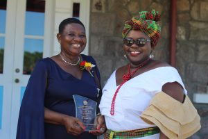 (L-r) Independence Day Awardee Mrs. Palsy Wilkin sharing a light moment with her sister Hon. Hazel Brandy-Williams after receiving a plaque from Her Honour Mrs. Hyleeta Liburd, Deputy Governor General on Nevis at an Awards Ceremony at Government House on September 20, 2021, in honour of her sterling contribution to Education in St. Kitts and Nevis on the occasion of the Federation's 38th Anniversary of Independence