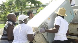 Hon. Alexis Jeffers, Area Representative for St. James' Parish, helps to load white goods onto a truck with the help of constituents of the St. James' Parish for disposal at the Long Point landfill during a clean-up exercise on October 16, 2021, in celebration of the 10th anniversary of his election to the Nevis Island Assembly
