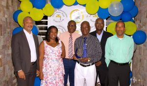 """Photo caption: (L-r) Hon. Spencer Brand, Minister of Water Services on Nevis; Ms. Tonya Bartlette, Manager of the Nevis Water Department; Mr. Denzil Stanley, Principal Assistant Secretary in the Ministry of Water Services; Mr. James """"Tin Tin"""" Caines, the longest serving of three retirees honoured by the Nevis Water Department; Dr. Ernie Stapleton, Permanent Secretary in the Ministry of Water Services and Mr. Roger Hanley, Operation Manager at the Nevis Water Department at a Retiree Cocktail celebration at the Nevis Performing Arts Centre on September 30, 2021"""